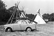 Teepee wooden poles on top of vintage car.Glastonbury, 1989.