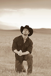 Cowboy praying in an open field
