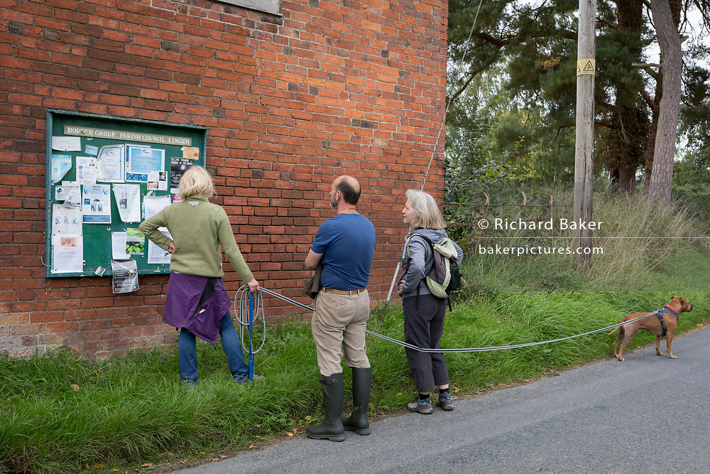Villagers on a country walk with their Staffordshire Bull Terrier pause to read the notices on a Parish Council community noticeboard, on 10th September 2018, in Lingen, Herefordshire, England UK.