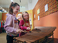 Collette Carrol (from left) and Katie Callahan, both 9 and of Westfield Elementary School, play a balafon together in the Western Africa exhibit at the African American Museum of Iowa in Cedar Rapids on Friday, March 22, 2013.