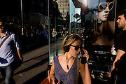 Young woman listens to mp3 music beneath a poster girl for Burberry sunglasses they call Eyewear, in a sunlit London street. Burberry Group plc is a British luxury fashion house, manufacturing clothing, fragrance, and fashion accessories.