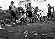 Gerardo, 14, shoots marbles with a group of friends in the streets of Los Pinos. The slum is one of the most notorious in Costa Rica.