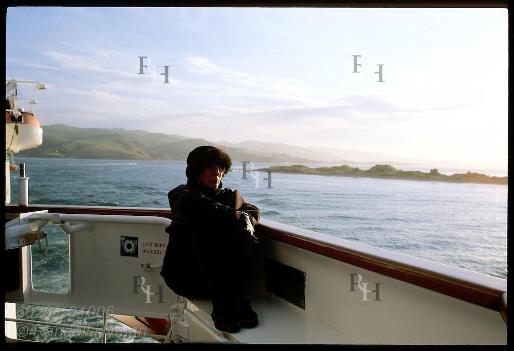 Well-bundled woman sits outside bridge on cruise ship Clipper Odyssey as it passes Otago Peninsula at sunset; Dunedin, NZ
