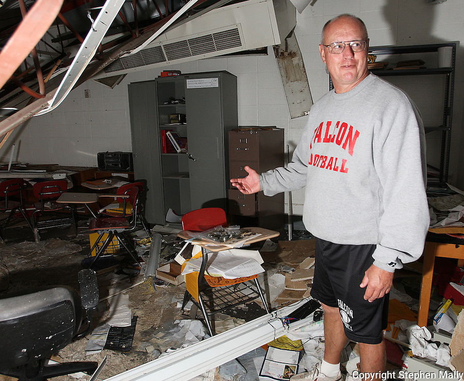 Ed Thomas, of Parkersburg, a teacher and football coach at Aplington-Parkersburg High School looks over the debris in his classroom and office in Parkersburg, Iowa on Wednesday June 4, 2008. (Stephen Mally for the New York Times)