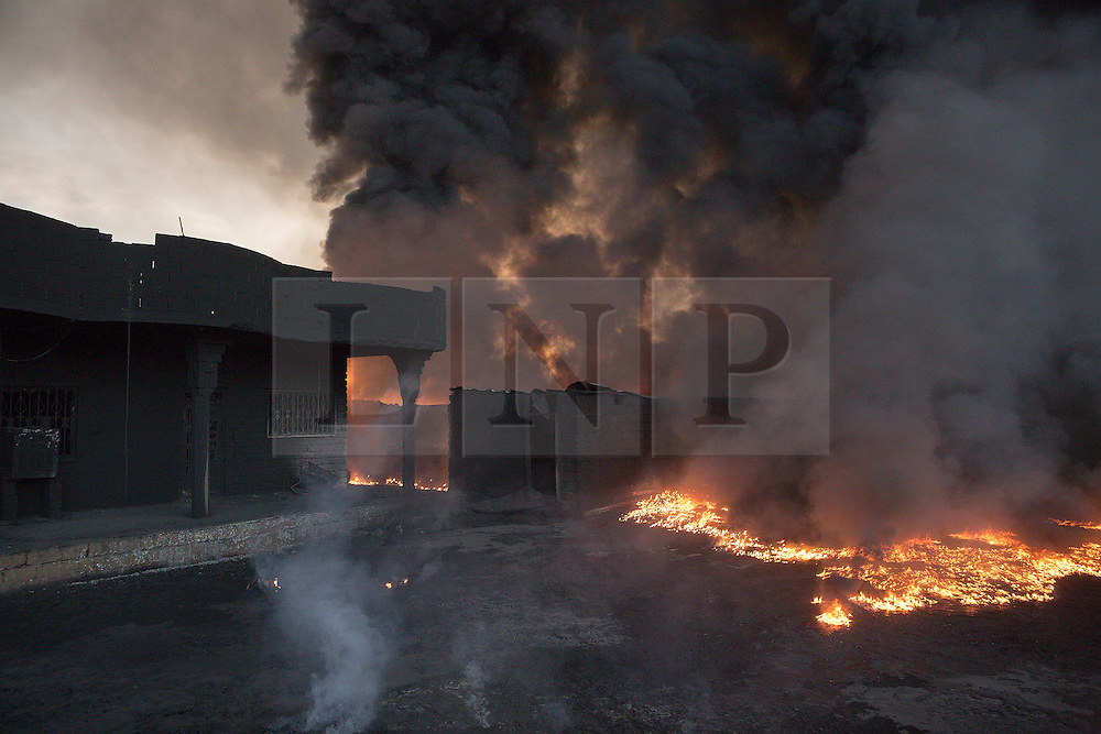 Licensed to London News Pictures. 20/10/2016. Oil burns in the garden of a home next to several burning wells in a residential neighbourhood in the town of Qayyarah, Iraq. The wells, part of a large oil field that surrounds the town, were set alight by retreating Islamic State militants as part of a scorched earth policy.<br /> <br /> Since being retaken from the Islamic State the town of Qayyarah has become an important staging post for the Iraqi Army, and some US support elements, in the buildup to the Mosul offensive. Photo credit: Matt Cetti-Roberts/LNP
