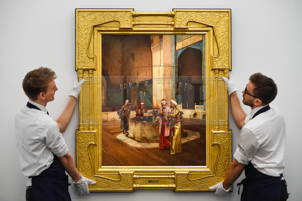 """© Licensed to London News Pictures. 11/10/2019. LONDON, UK. Technicians present """"After Prayers"""" by Rudolf Ernst, (Est GBP300-400k).  Preview of works from the Najd Collection of orientalist paintings at Sotheby's in New Bond Street, which record daily life in the historic Arab, Ottoman and Islamic worlds  All 155 paintings are on public view 11- 15 October, with 40 works to be auctioned on 22 October.  Photo credit: Stephen Chung/LNP"""