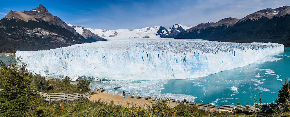 Visit Perito Moreno Glacier in Los Glaciares National Park as a day trip from El Calafate, in southwest Santa Cruz province, Argentina. Easy boardwalks give wide views of Moreno Glacier, an impressive wall of ice 200 feet high and 3 miles (5 km) wide flowing into Lake Argentina. The glacier flows up to 2300 feet thick and originates in the huge Hielo Sur (Southern Icefield) in the southern Andes mountains. For the past 90 years, its advancing has equaled melting (up to 2 meters per day, 700 meters per year), and the terminus has stayed at one location. Flowing ice periodically dams an arm of the lake which rises for a few years then breaks across the nose of the glacier as a crashing river (in March 2004 and 1991). In this 2005 photo, a narrow river flowed across the glacier face which calved large chunks of ice into the water with a loud crash several times per day. The foot of South America is known as Patagonia, a name derived from coastal giants, Patagão or Patagoni, who were reported by Magellan's 1520s voyage circumnavigating the world and were actually Tehuelche native people who averaged 25 cm (or 10 inches) taller than the Spaniards. Panorama stitched from 3 overlapping photos.