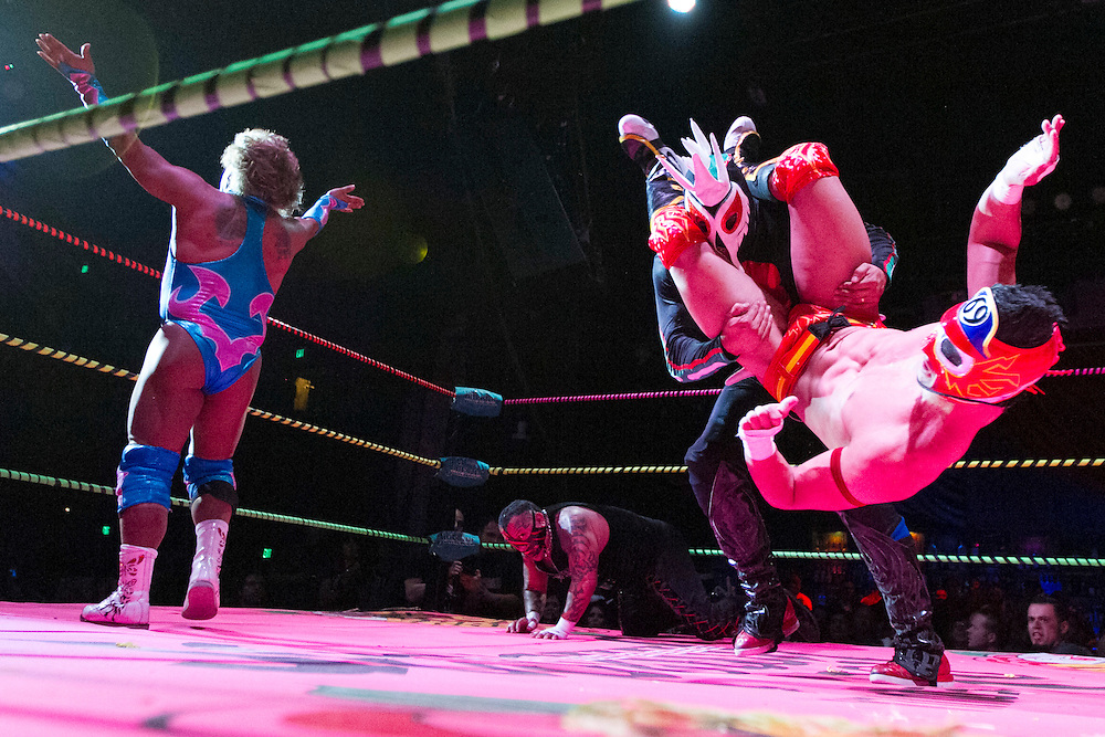 Luchador El Bombero (far right) flips opponent Chupacabra as Cassandro (left) faces the crowd during the main event at Lucha VaVoom's Halloween Ring of Terror show at the Mayan Theater on Wednesday, October 26, 2011 in downtown Los Angeles. Lucha VaVoom is a Mexican masked wrestling and saucy striptease show. (Photo by Michael Yanow)