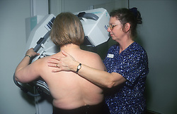 Woman with technician undergoing mammography examination at breast screening unit,
