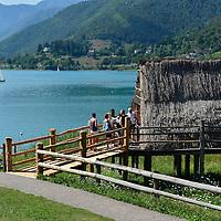 Palafitta del Lago di Ledro con sfondo barca a vela