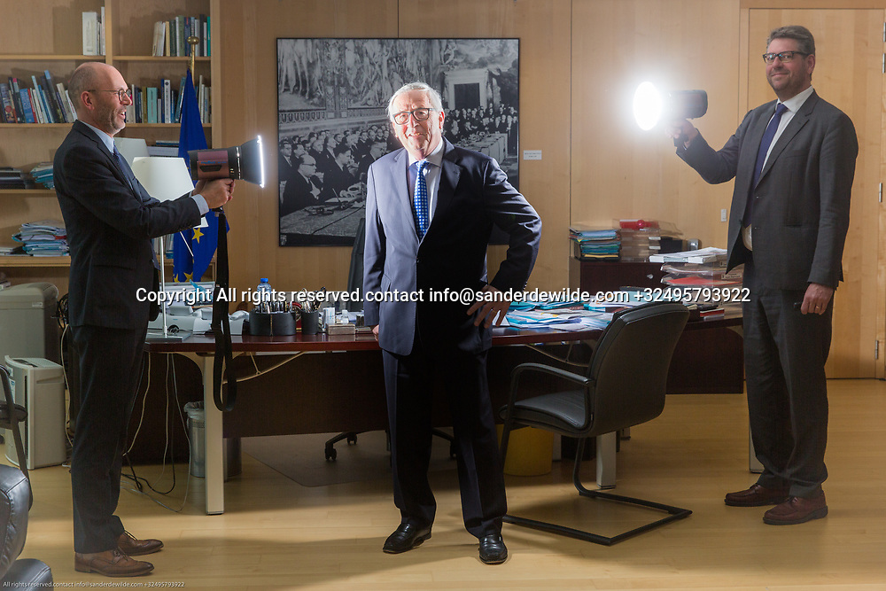 Brussels Belgium April 12 2018 President of ther European Commission Jean-Claude Juncker portrayed at his office on the topfloor of the Berlaymont building.two journalists of Dutch daily TRouw aiming lights at him in front of his desk.Christoph Schmidt right, Stevo at the left of mr Juncker.