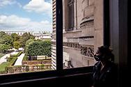 Woman watching landscape from Louvre window.