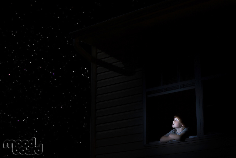 Teenage boy looks up at night sky