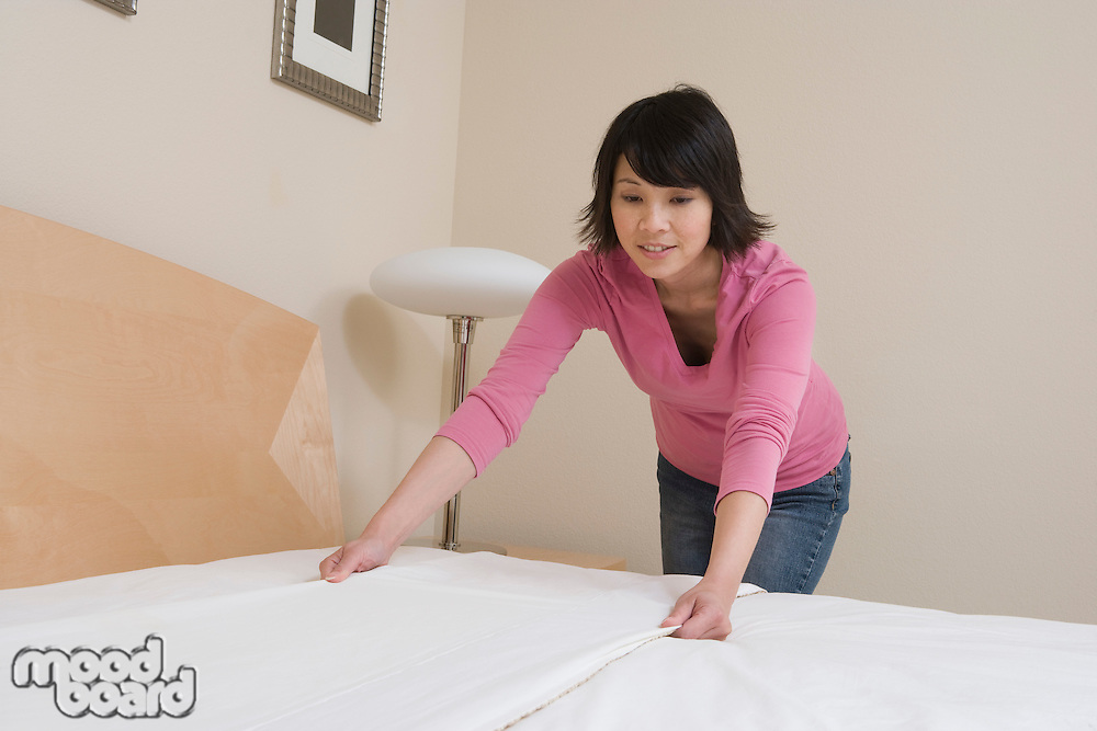 Mid-adult woman making a bed