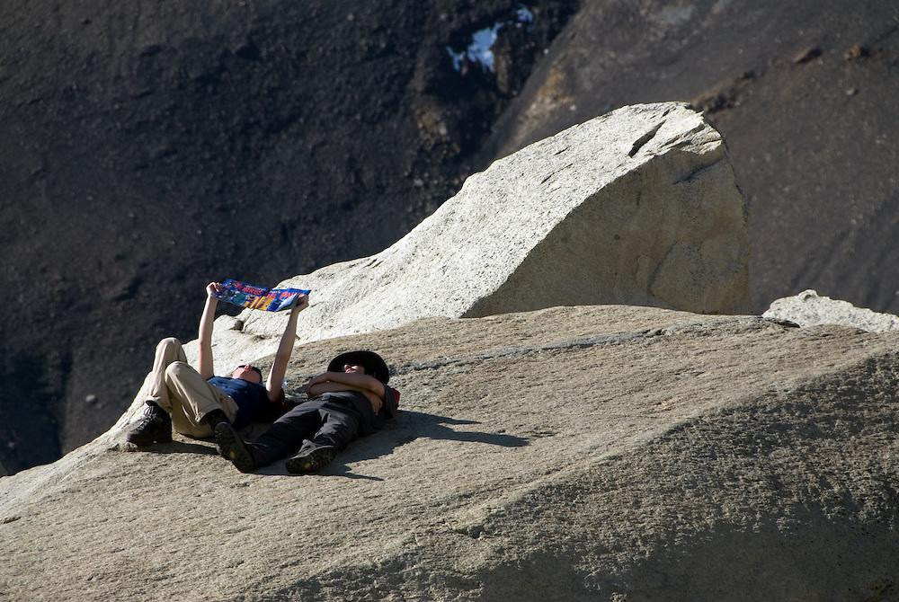 Hikers reading park brochure on a boulder below Torres Del Paine, Torres Del Paine National Park, Chile.