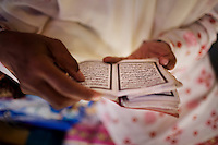 An Acehnese woman reads the koran on the street, in Banda Aceh, Indonesia, Thursday, Nov. 19, 2009. The city enforces a moderate form of Islamic Law.