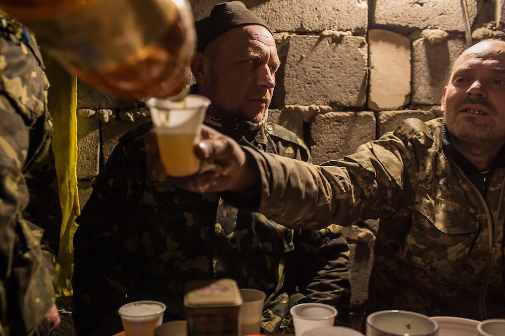 PISKY, UKRAINE - NOVEMBER 17, 2014: A member of the Ukrainian army pours a cup of beer for a fellow soldier inside the abandoned building being used as their base in the fight against pro-Russia rebels for control of the Donetsk airport, in Pisky, Ukraine. CREDIT: Brendan Hoffman for The New York Times