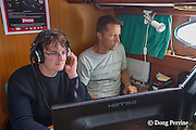 Tethys Research Institute researcher Sylvan Oehen analyzes acoustic data on computer while research assistant Filippo Santini monitors cetacean calls on hydrophone, aboard R/V Pelagos, Ligurian Sea, Mediterranean Sea, Italy