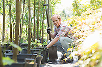 Portrait of happy gardener crouching while holding shovel at plant nursery