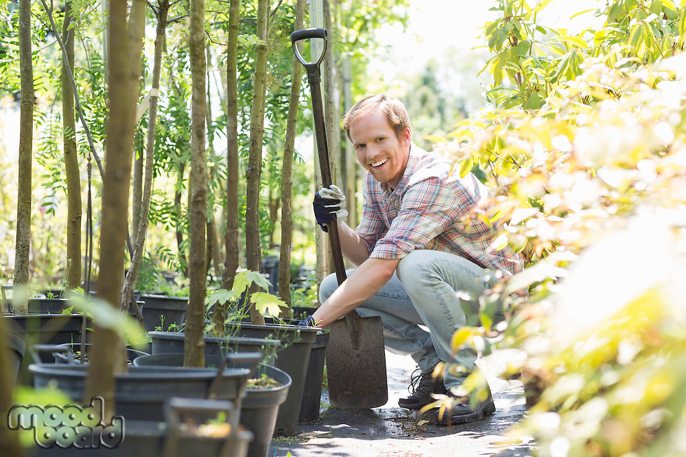Portrait of happy gardener crouching while holding shovel at plant nursery