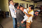 20 MAY 2013 - MAE KASA, TAK, THAILAND:  Dr. FRANCOIS NOSTEN, Director of the Shoklo Malaria Research Unit, helps a Burmese patient with malaria who collapsed in the waiting area of the SMRU clinic in Mae Kasa, Thailand.  PHOTO BY JACK KURTZ