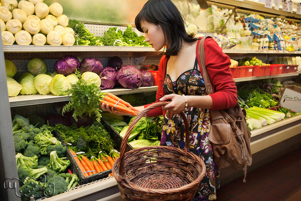 Young woman shopping for vegetables in farmer's market