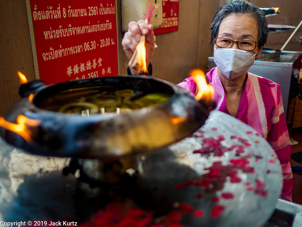 29 JANUARY 2019 - BANGKOK, THAILAND:       A woman lights incense before praying the Poh Teck Tung shrine in Bangkok's Chinatown. Chinese temples in Bangkok are getting crowded at people come to the temples to pray ahead of the Lunar New Year. Chinese New Year celebrations in Bangkok start on February 4, 2019. The coming year will be the Year of the Pig in the Chinese zodiac. About 14% of Thais are of Chinese ancestry and Lunar New Year, also called Chinese New Year or Tet is widely celebrated in Chinese communities in Thailand.   PHOTO BY JACK KURTZ