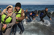 Asylum seekers wade through the Aegean Sea upon arriving on the island of Lesvos, Greece from the North coast of Turkey in a rubber raft on November 16, 2015.