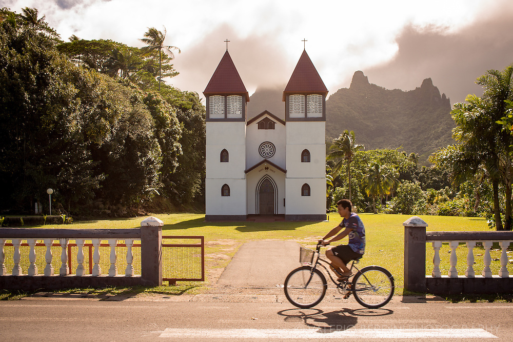 A cyclist rides is bike along a road in Moorea in front of a countryside church