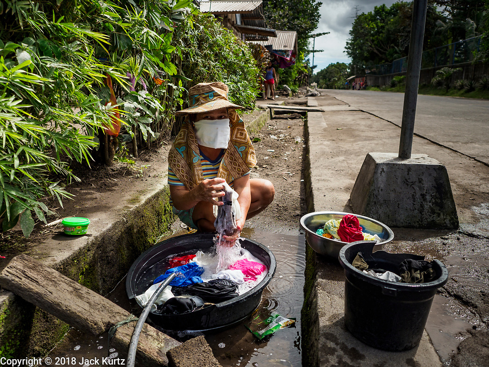 23 JANUARY 2018 - GUINOBATAN: ALBAY, PHILIPPINES: A woman wears a face mask because of the Mayon volcano's ash fall while she does her laundry in Guinobatan. The Mayon volcano continued to erupt Tuesday, although it was not as active as it was Monday. There were ash falls in communities near the volcano. This is the most active the volcano has been since 2009. Schools in the vicinity of the volcano have been closed and people living in areas affected by ash falls are encouraged to stay indoors, wear a mask and not participate in strenuous activities.    PHOTO BY JACK KURTZ