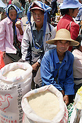 A Chinese rice farmers sell bags of rice at a weekly market in Lunan, Yunnan Province. The Chinese government has been evaluating the proposed release of genetically modified rice in the country but has not yet approved any varieties due to unresolved environmental, health and economic issues.