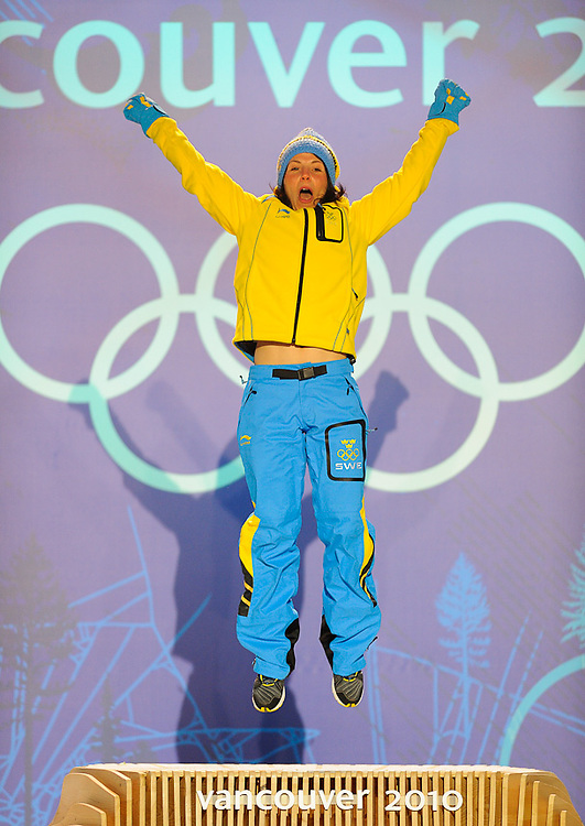 Sweden's Charlotte Kalla jumps in celebration on the podium after winning the gold medal in ladies 10km free during the medal ceremony at Whistler on Day 4 of the Vancouver 2010 Winter Olympic Games.