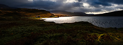 The ruins of Calda House on the shore of Loch Assynt during rainy weather.