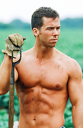shirtless man holding a hoe on a farm