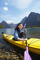Woman paddling kayak in mountain lake