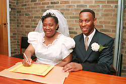 Newly married bride and groom signing marriage register,