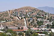 A metal wall, as seen from Arizona, marks the international border between Nogales, Arizona, USA, and Nogales, Sonora, Mexico.