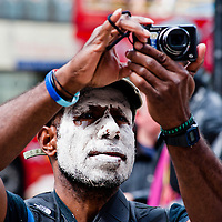 London, UK - 15 June 2012: activist covered in clay takes a picture during the Carnival of Dirt. More than 30 activist groups from London and around the world have come together to highlight the alleged illicit deeds of mining and extraction companies.