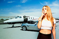 Portrait of young woman smoking cigarette with car and airplane in the background