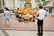 26 MARCH 2010 - BANGKOK, THAILAND: People pray at the Erawan Shrine in Bangkok. The Erawan Shrine (Thai: San Phra Phrom) is a Hindu shrine in Bangkok, Thailand that houses a statue of Phra Phrom, the Thai representation of the Hindu creation god Brahma. The Erawan Shrine was built in 1956 as part of the government-owned Erawan Hotel to eliminate the bad karma believed caused by laying the foundations on the wrong date. The hotel's construction was delayed by a series of mishaps, including cost overruns, injuries to laborers, and the loss of a shipload of Italian marble intended for the building. Furthermore, the Ratchaprasong Intersection had once been used to put criminals on public display. An astrologer advised building the shrine to counter the negative influences. The Brahma statue was designed and built by the Department of Fine Arts and enshrined on 9 November 1956. The hotel's construction thereafter proceeded without further incident.      PHOTO BY JACK KURTZ