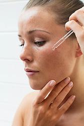 Beauty Portrait of Woman Applying Serum