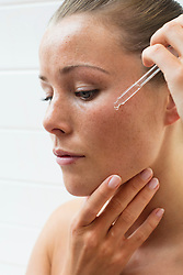 Beauty Portrait of Woman Applying Serum