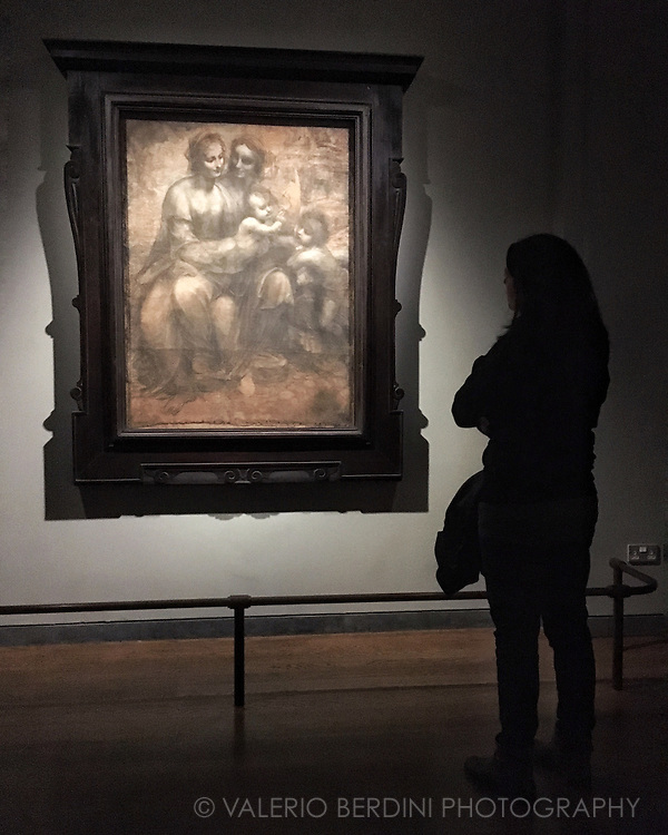 A woman stands in front of Leonardo Da Vinci The Virgin and Child with St Anne and St John the Baptist, also known as The Burlington House Cartoon at the National Gallery in London.