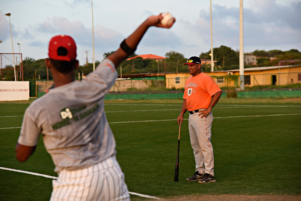 WILLEMSTAD, CURACAO - DECEMBER 11, 2014: Some of Curacao's best senior league players are put through drills for development at the Dutch Caribbean Baseball Academy in Santa Rosa to make them more viable for American college baseball programs as well as the major leagues. Coach Ben Thijssen, right, watches senior league players (15-19 years old) warm up, correcting their form and offering advice. (photo by Melissa Lyttle)