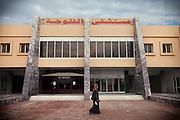 A woman is walking by a building of the Fallujah General Hospital, Iraq. Around 15 per cent of children at the hospital are now being born with some sort of congenital defect. The average elsewhere in the world is believed to be between 2 and 4 per cent.