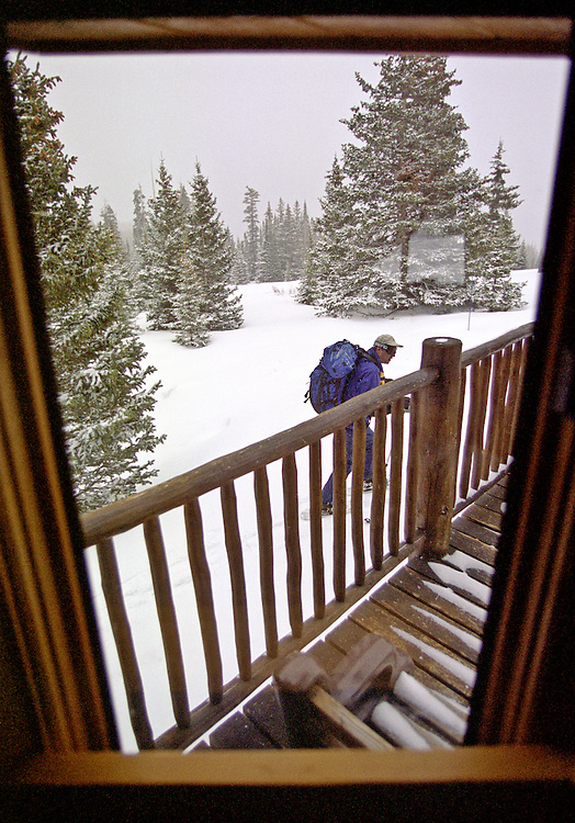 A man snowshoes from a high mountain cabin in the Colorado Rocky Mountians.