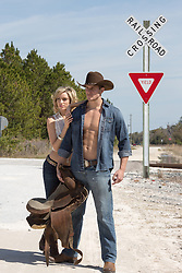 cowboy and a beautiful woman standing near railroad crossing in rural America