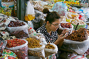 Phnom Penh, Cambodia. Central Market. Vendor with smartphone.
