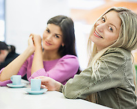 Portrait of young businesswomen smiling at cafeteria table