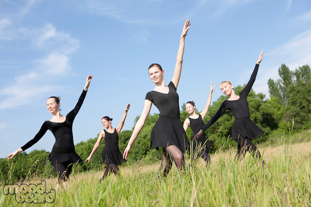 Young women dance in a field